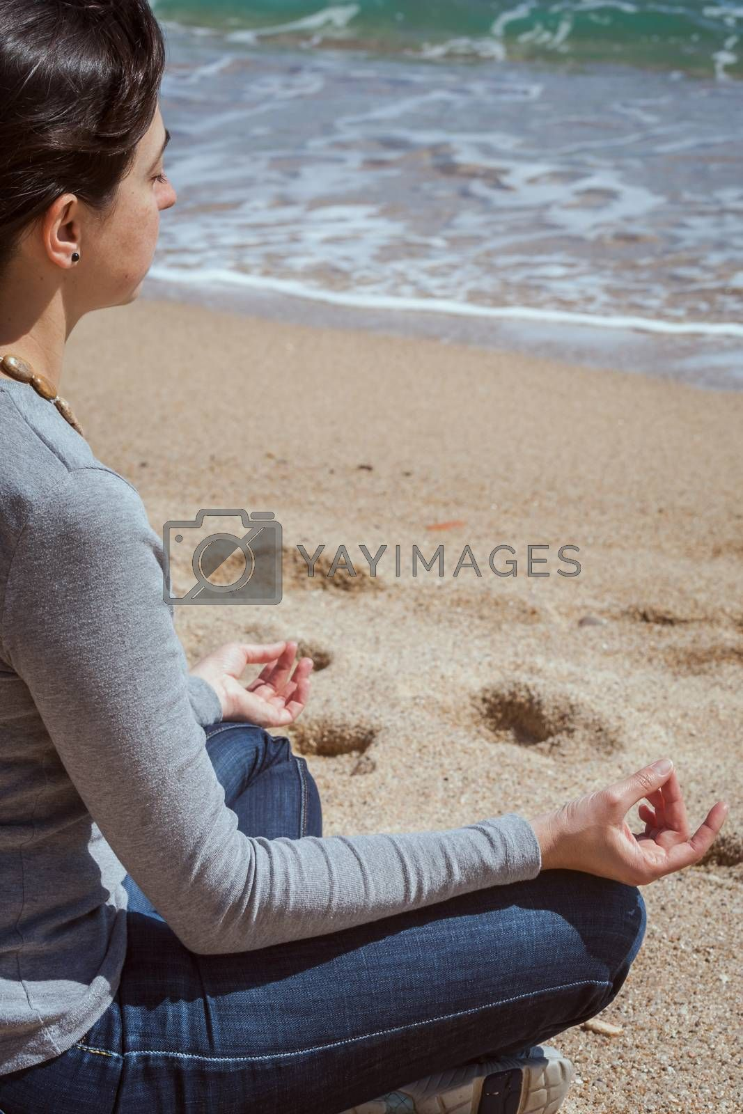 Body detail of a beautiful girl in a meditation on the beach
