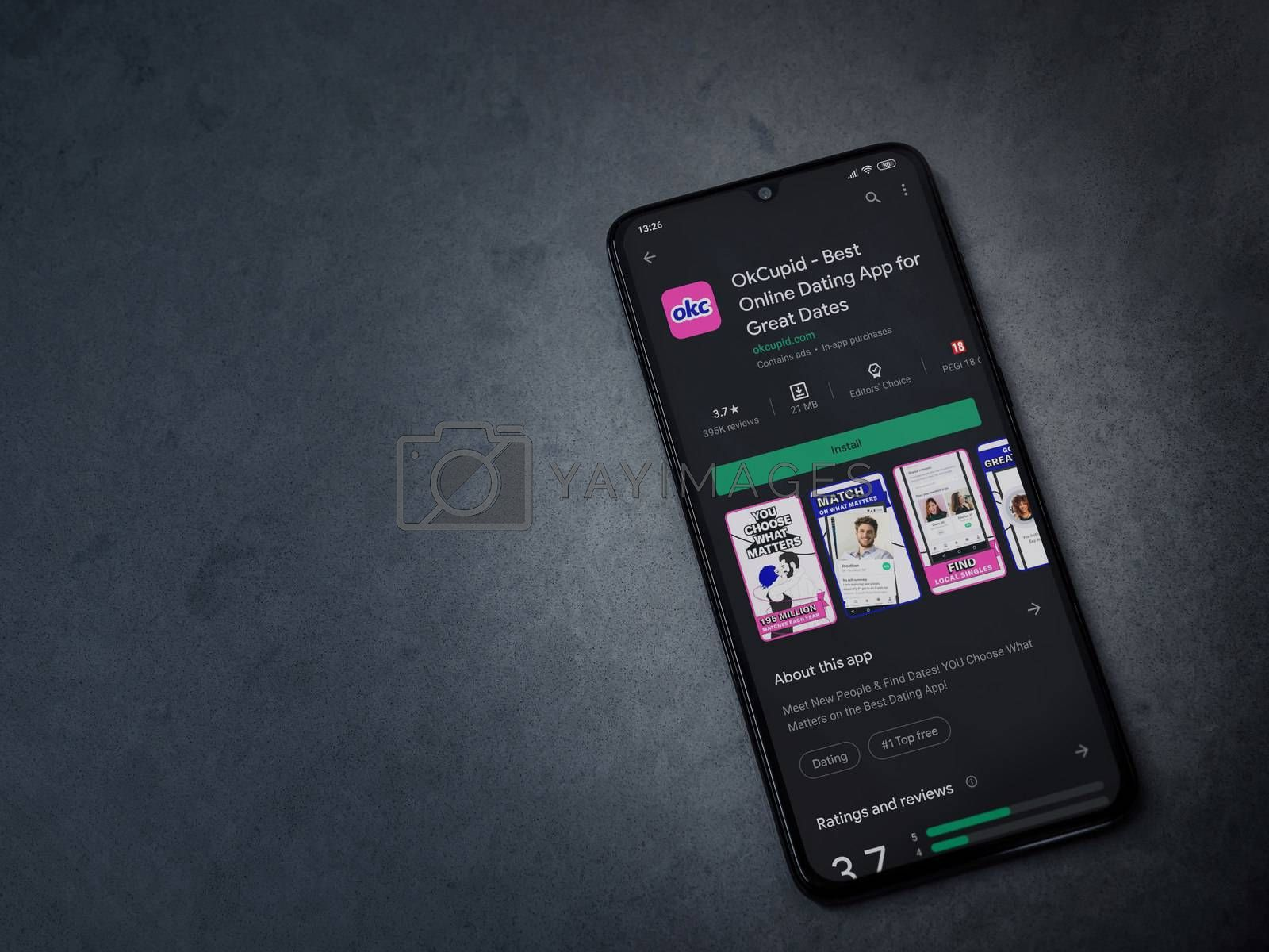 Lod, Israel - July 8, 2020: OkCupid app play store page on the display of a black mobile smartphone on dark marble stone background. Top view flat lay with copy space.