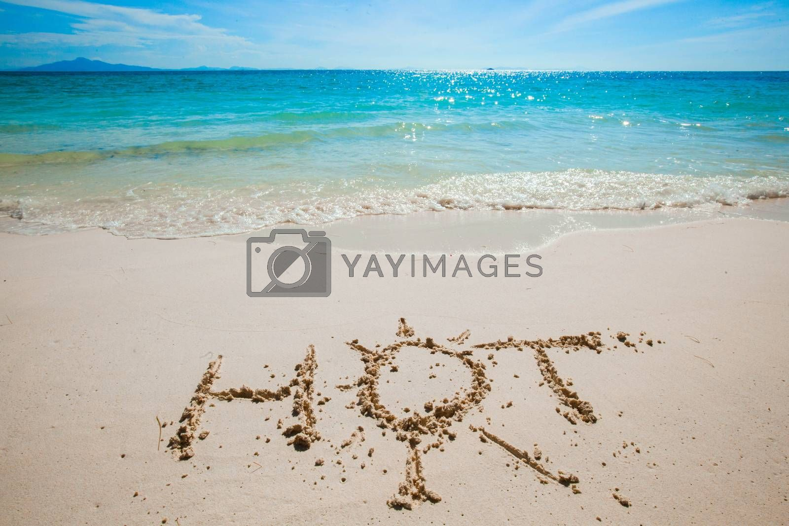 HOT word and sun symbol written on the sand of tropical sea beach