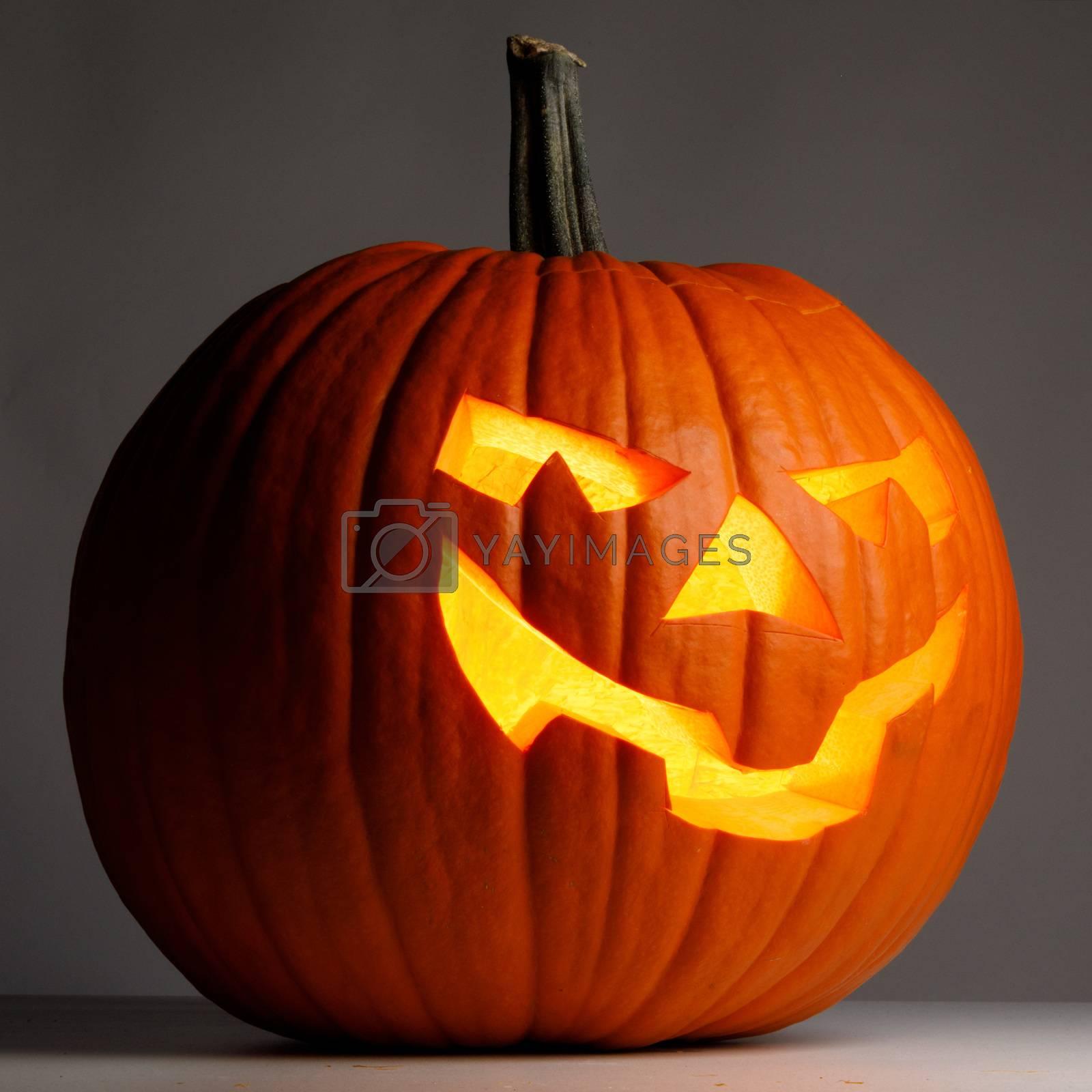 Glowing Halloween Pumpkin on dark background close up