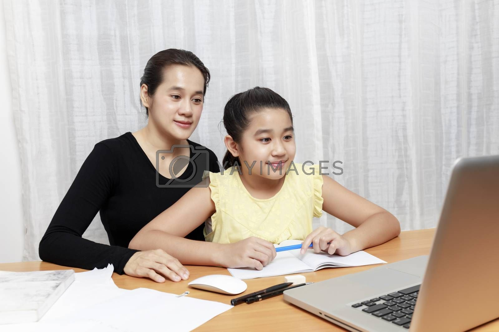 Asian young little girl using pencil to do homework with her mother. Student kid writing  homework book. Girl use computer to study at home. Education homeschool  concept.