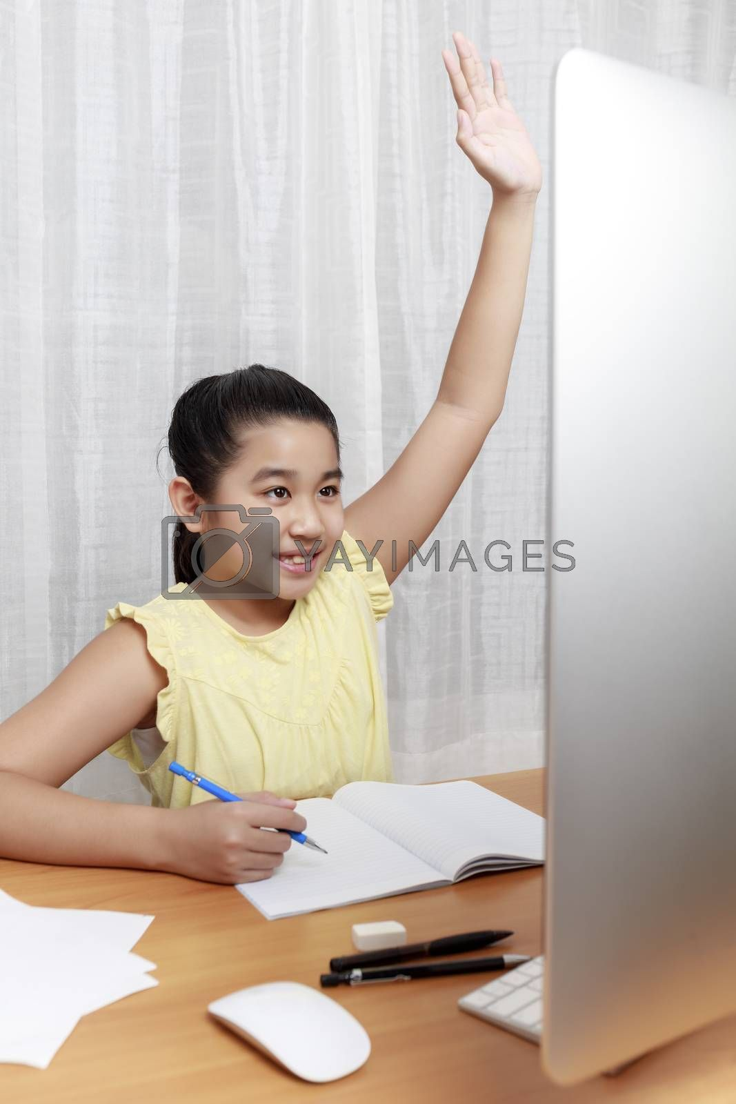 Asian little girl is studying online via the internet  sitting and writing in living room at home. Asia children writing with pencil on paper notebook online learning at home, learn from home concept