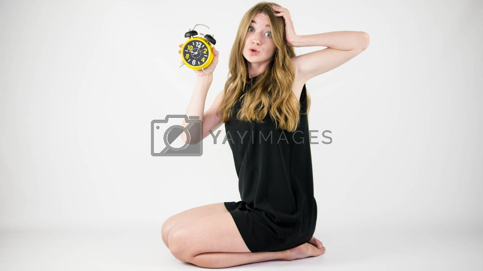 A girl with a retro clock in her hands,holding her head with her hand,thinking about the time,the surprised face of a young and beautiful girl in a black dress.
