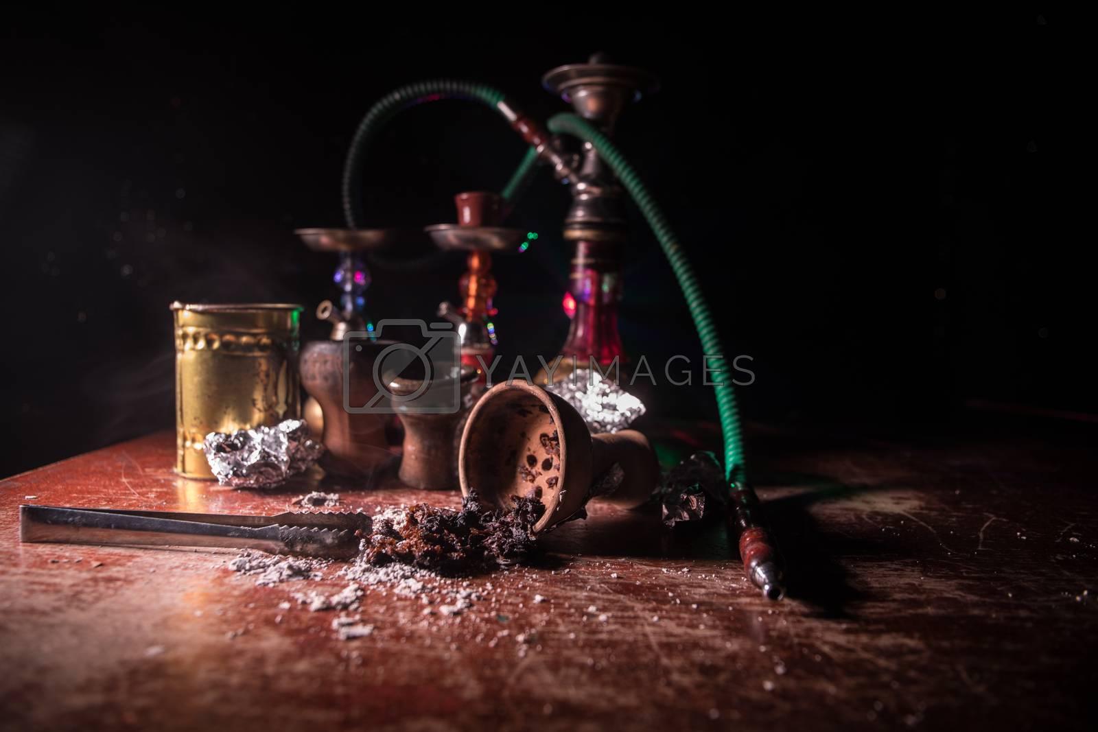 Shisha concept. Preparing shisha on table. Used shisha bowl on wooden table. Dark atmosphere with light. Selective focus.