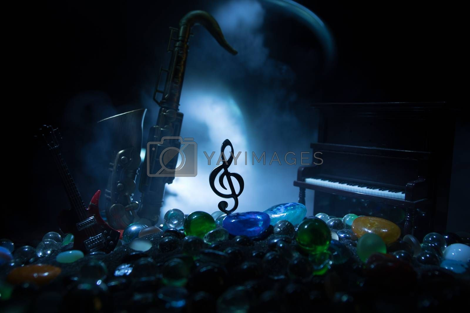 Music concept. Musical symbol treble clef stainless steel miniature with colorful toned light on foggy background. Musical instruments in lowlight. Selective focus