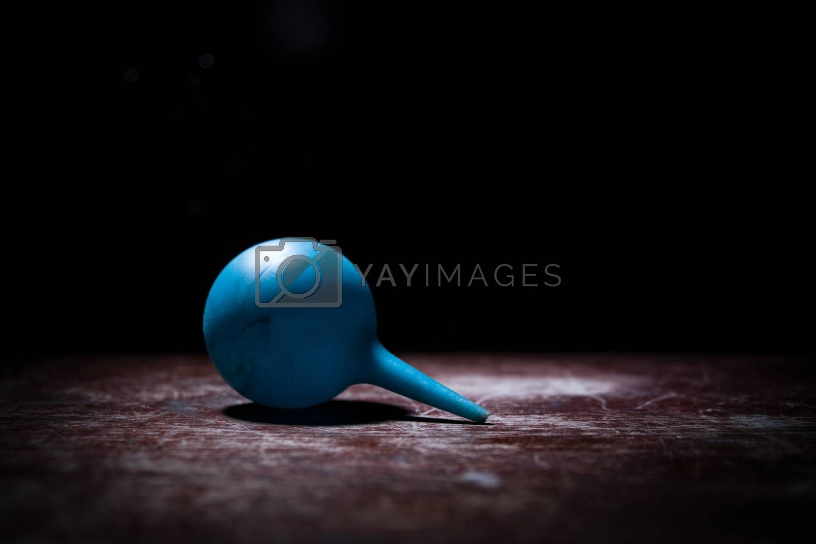 Blue enema on dark background with backlight. Creative artwork decorated with light. Selective focus