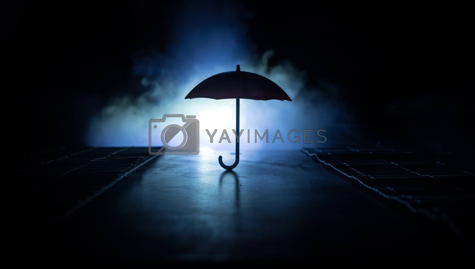 Silhouette of umbrella miniature on table with dark toned foggy background. Creative concept. Selective focus