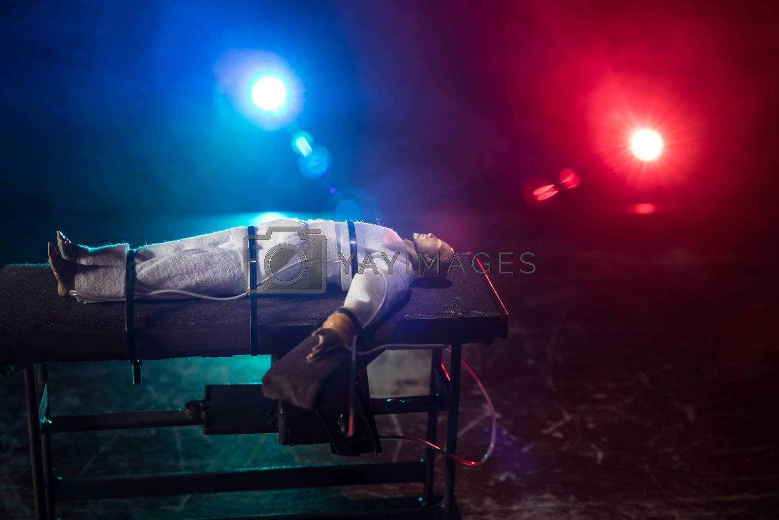 Lethal injection concept. Prisoner handcuffed to death by lethal injection. Creative artwork decoration with scale model on dark with lights.