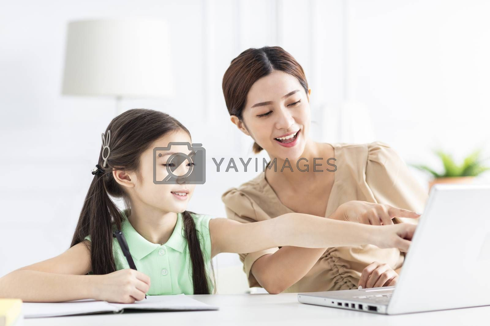 Mother with daughter watching the laptop and working at home