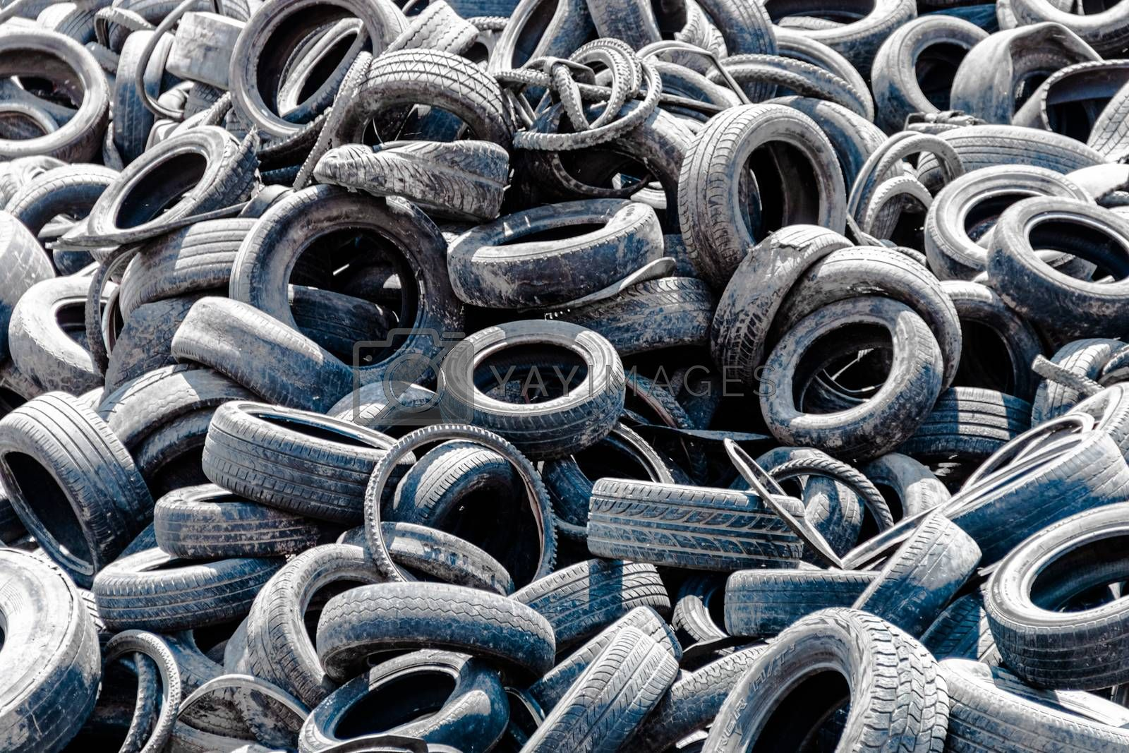 Assorted pile of old and used automotive road tires, showing a variety of tread patterns in a tires shop back yard. No people. Copy space