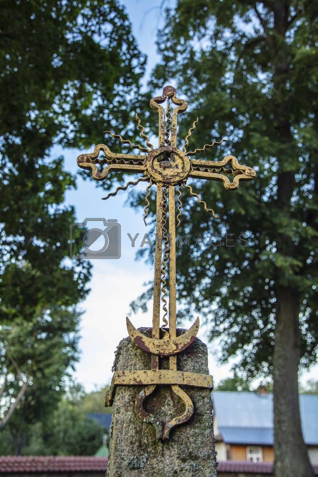 old metal cross, trees and sky in the background