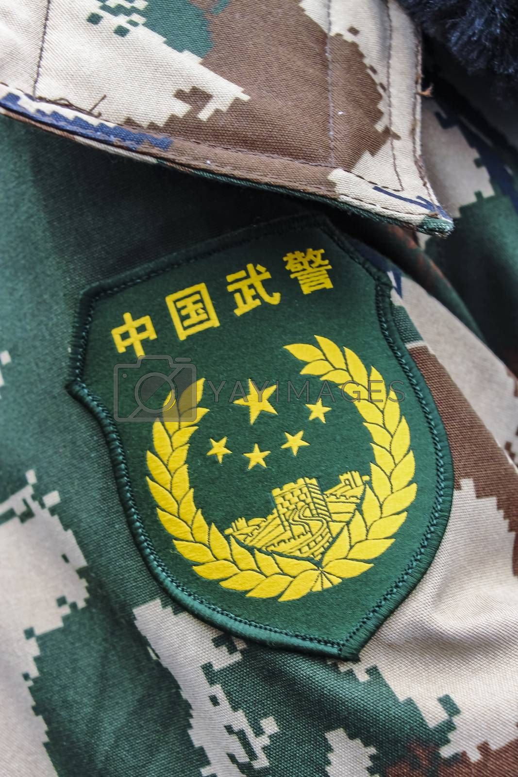 Emblem of the Chinese People's Armed Police Force over camouflage army fatigues