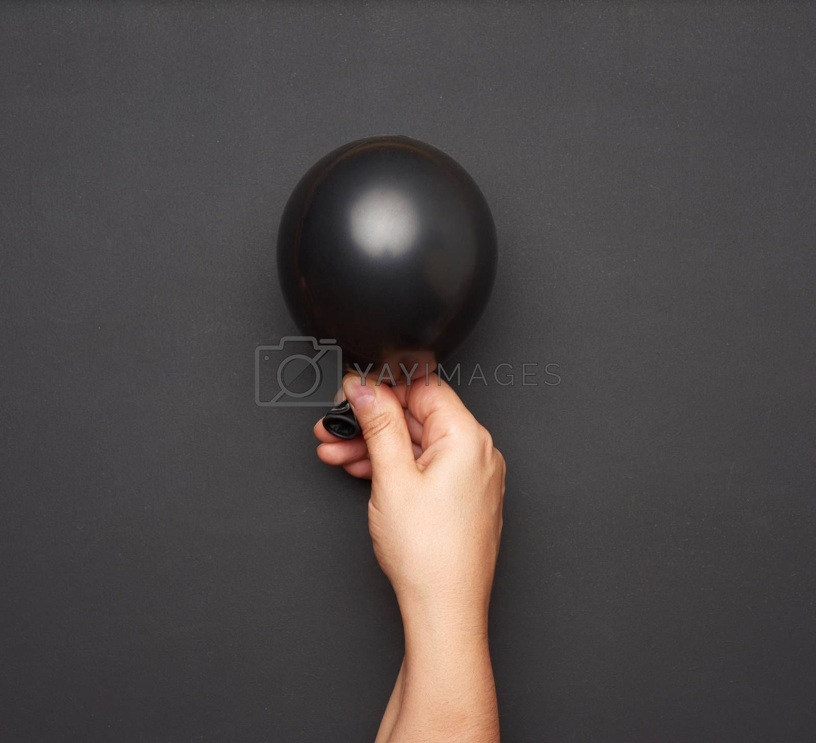 female hand holding an inflated black air balloon on a black background, close up
