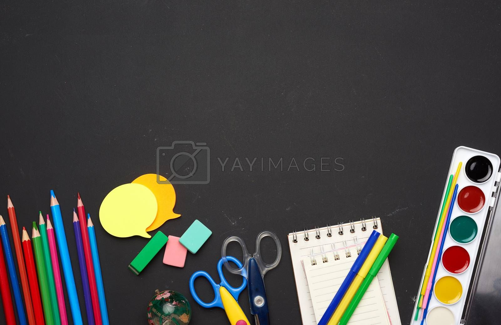 colorful wooden pencils, scissors, notepads and paint for drawing on a blank black chalk board, school stationery, copy space