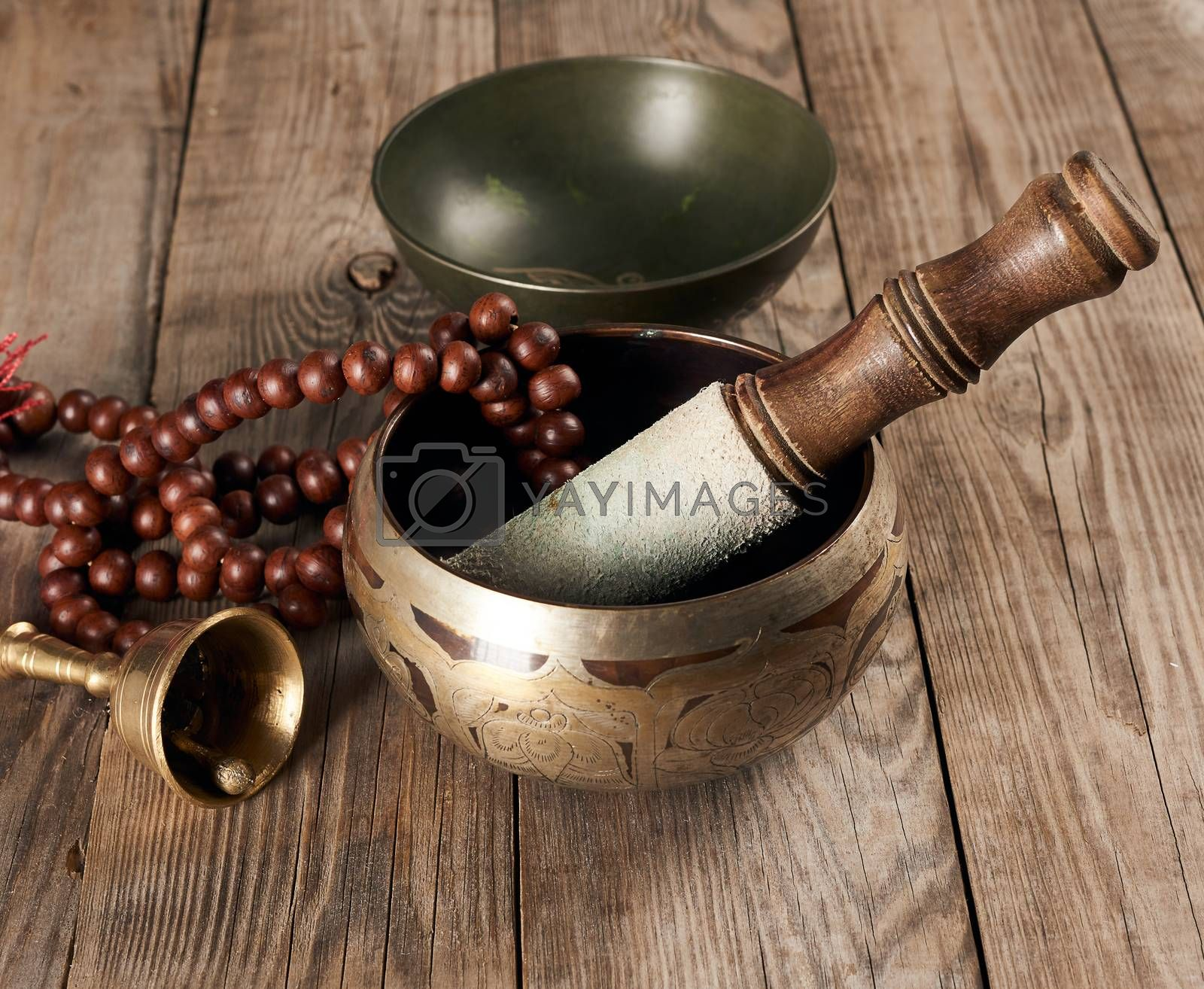 Tibetan singing copper bowl with a wooden clapper on a brown wooden table, objects for meditation and alternative medicine, close up