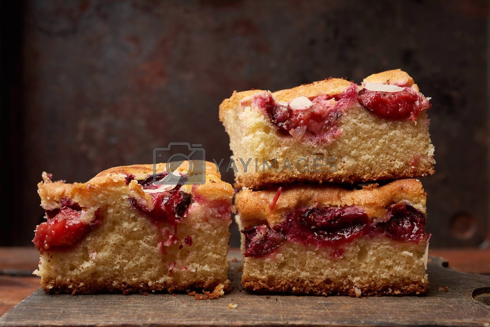 stack of square baked sponge cake slices with plums on wooden kitchen board, close up