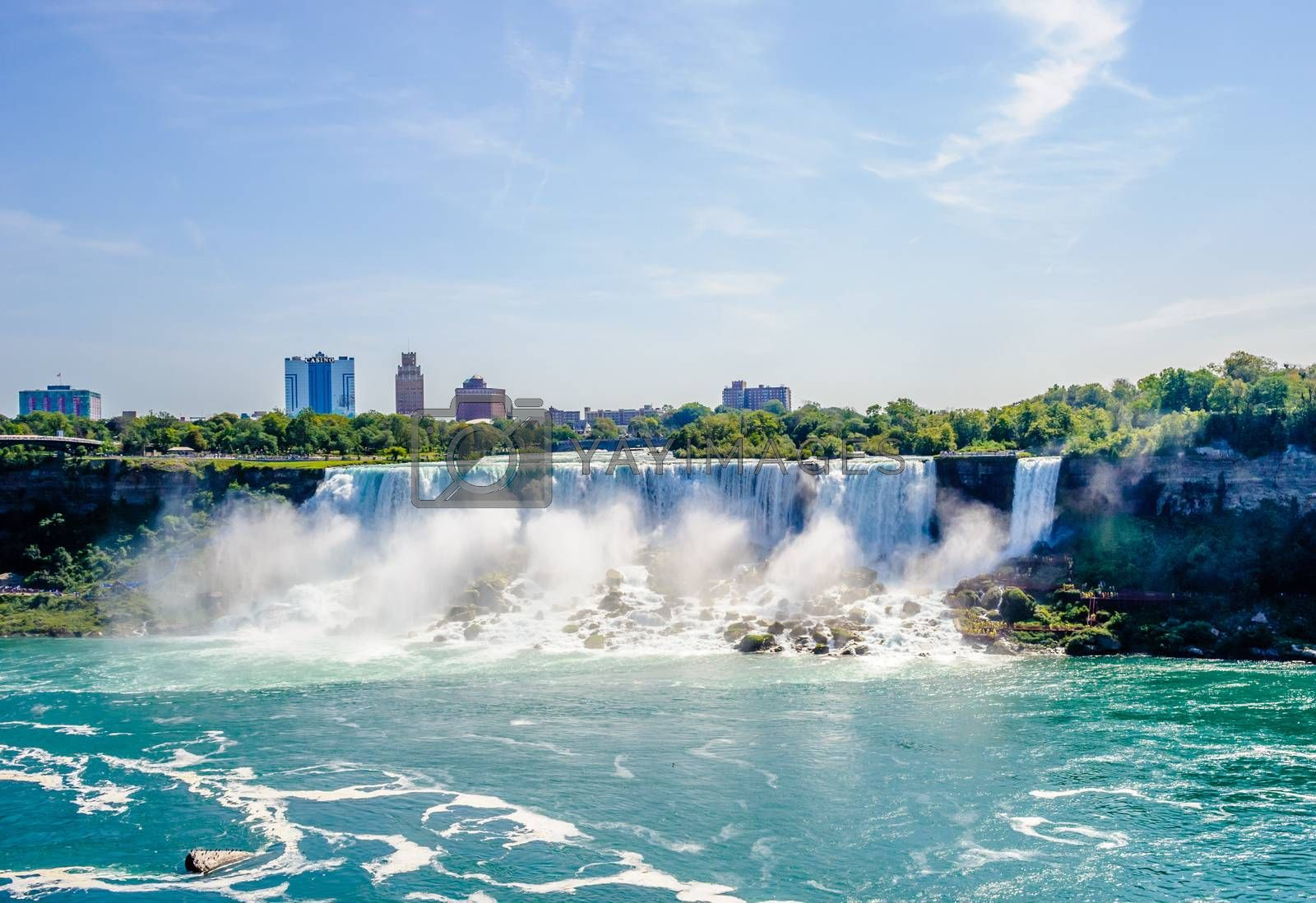 NIAGARA FALLS, CANADA - AUGUST 27, 2017: The American Falls and nearby buildings are visible from across the Niagara River.
