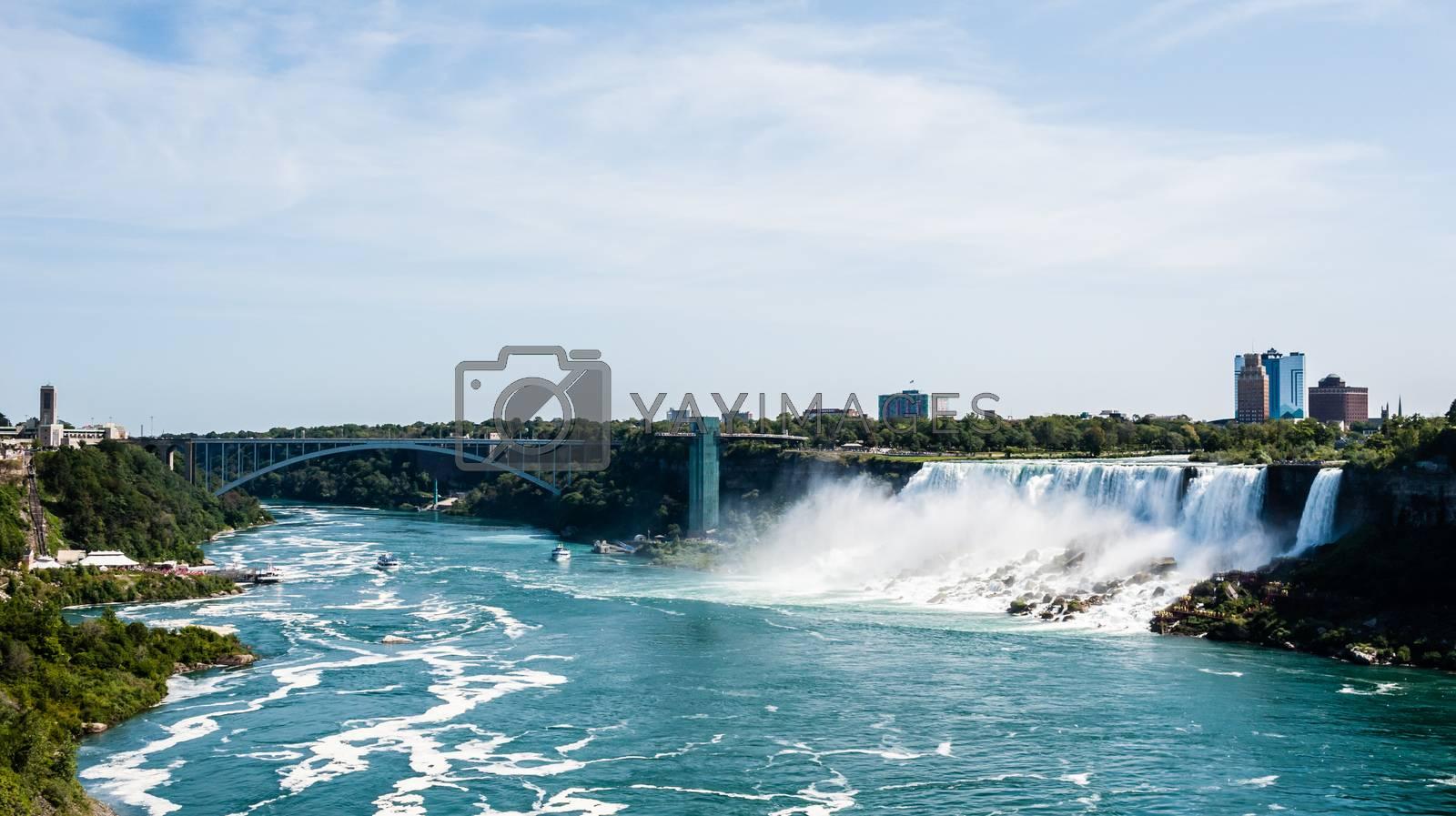 NIAGARA FALLS, CANADA - AUGUST 27, 2017: Tour boats pass under the Rainbow Bridge on the Niagara River to visit the waterfalls.