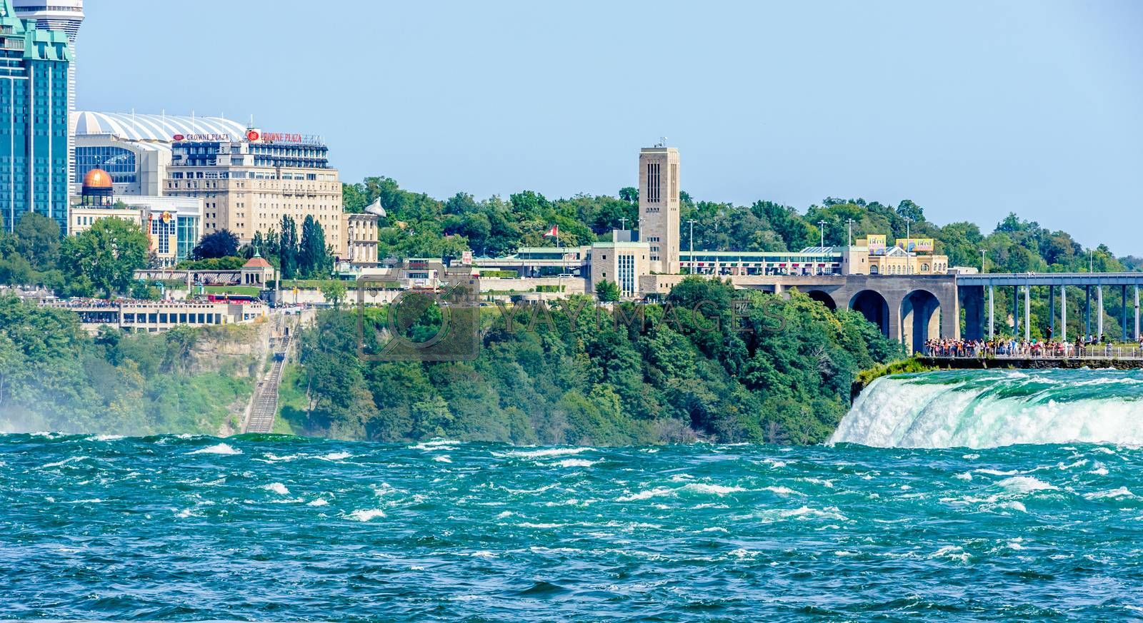NIAGARA FALLS, CANADA - AUGUST 27, 2017: Tourists view the Horseshoe Falls from a platform on the American side, opposite the border crossing and city on the Canadian side.