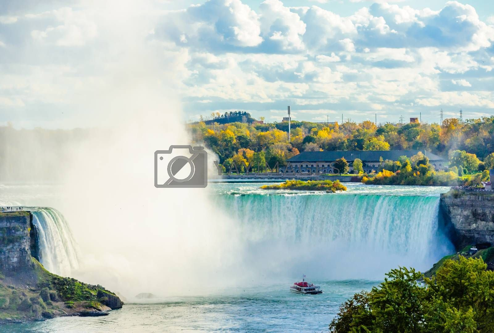 NIAGARA FALLS, CANADA - OCTOBER 26, 2017: A tour boat gets close to the Horseshoe Falls surrounded by colorful autumn trees.