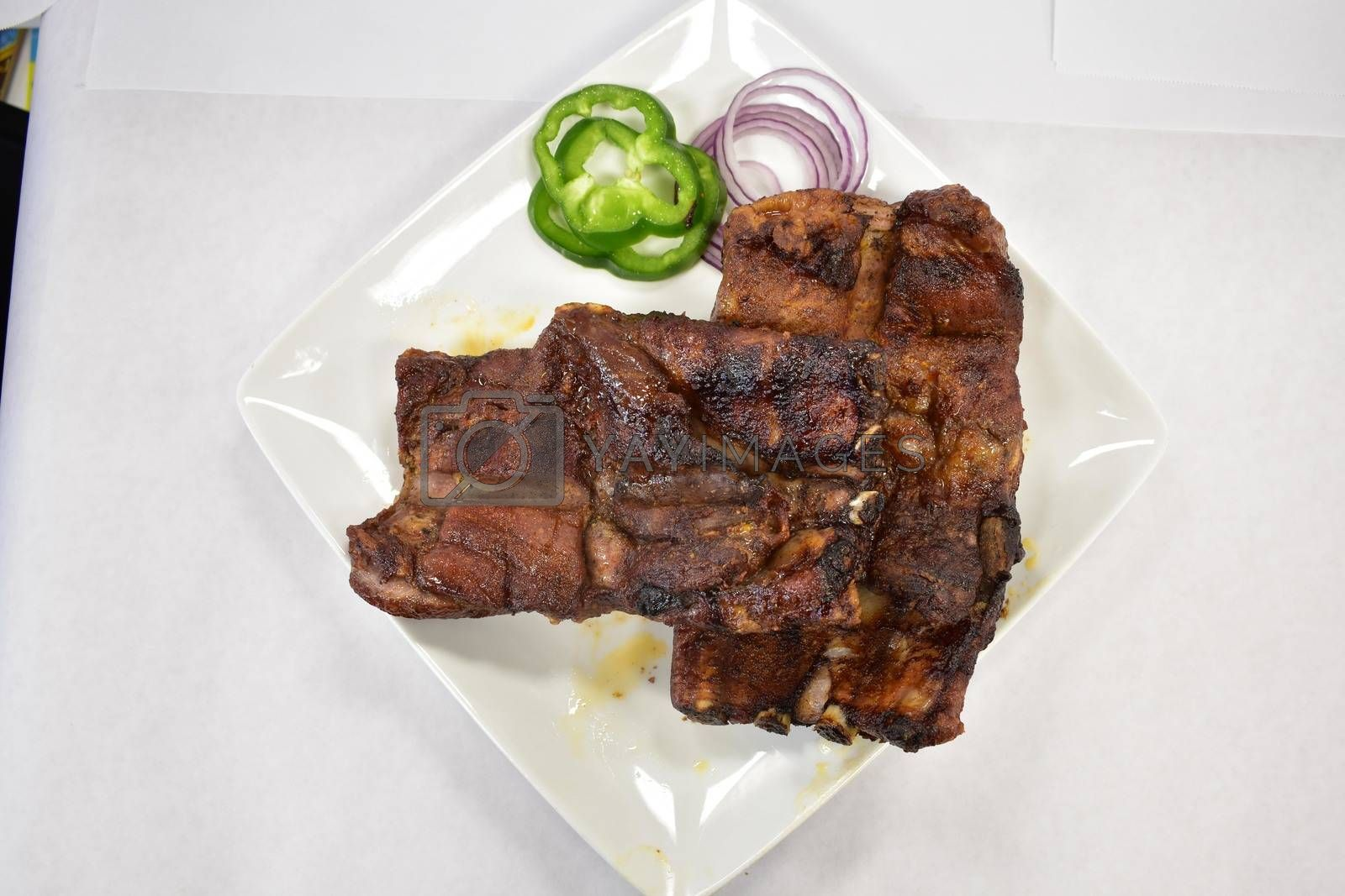 A Well-Done Rack of Ribs Plated on a White Background