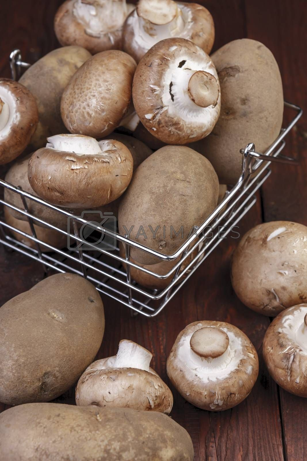 A metal wire basket filled with potatoes and mushrooms on a wooden table.