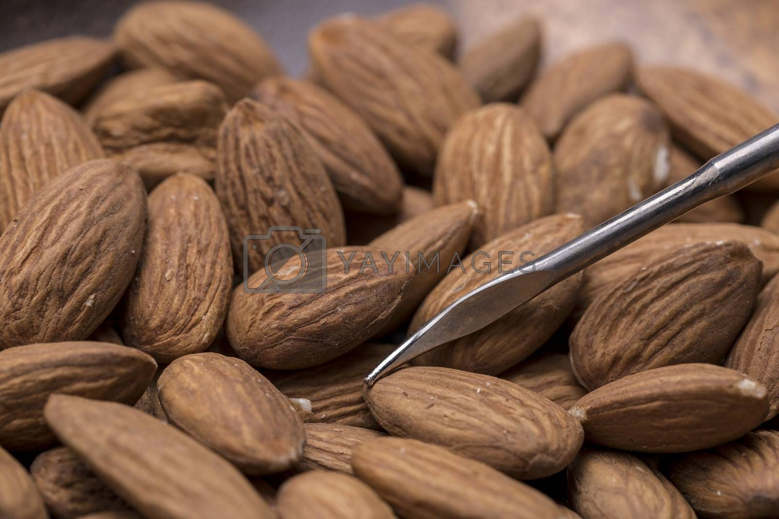 A close up of fresh shelled almonds on a wooden plate.