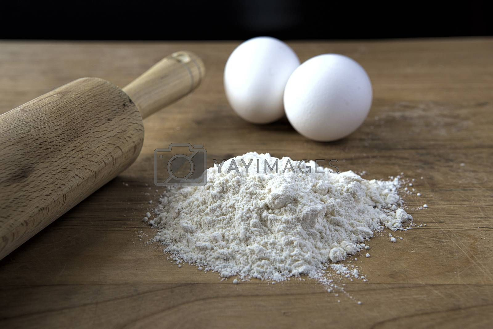 A concept photo of flour in a pile, two eggs, and a rolling pin.