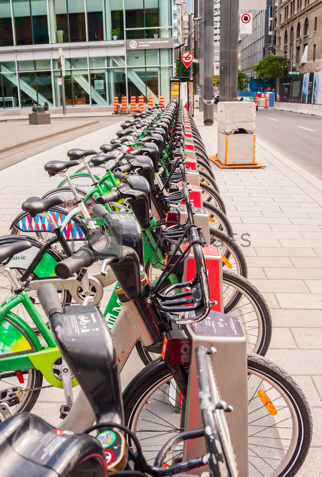 MONTREAL, CANADA - JUNE 17, 2018: The city's Bixi rental bicycles are lined up at one of the many automated docking stations downtown.