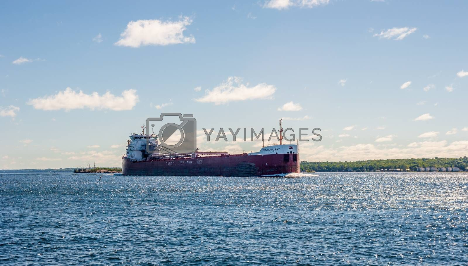 """BROCKVILLE, ONTARIO, CANADA - JUNE 19, 2018: The lake freighter """"Thunder Bay"""" travels along the St. Lawrence River heading west."""