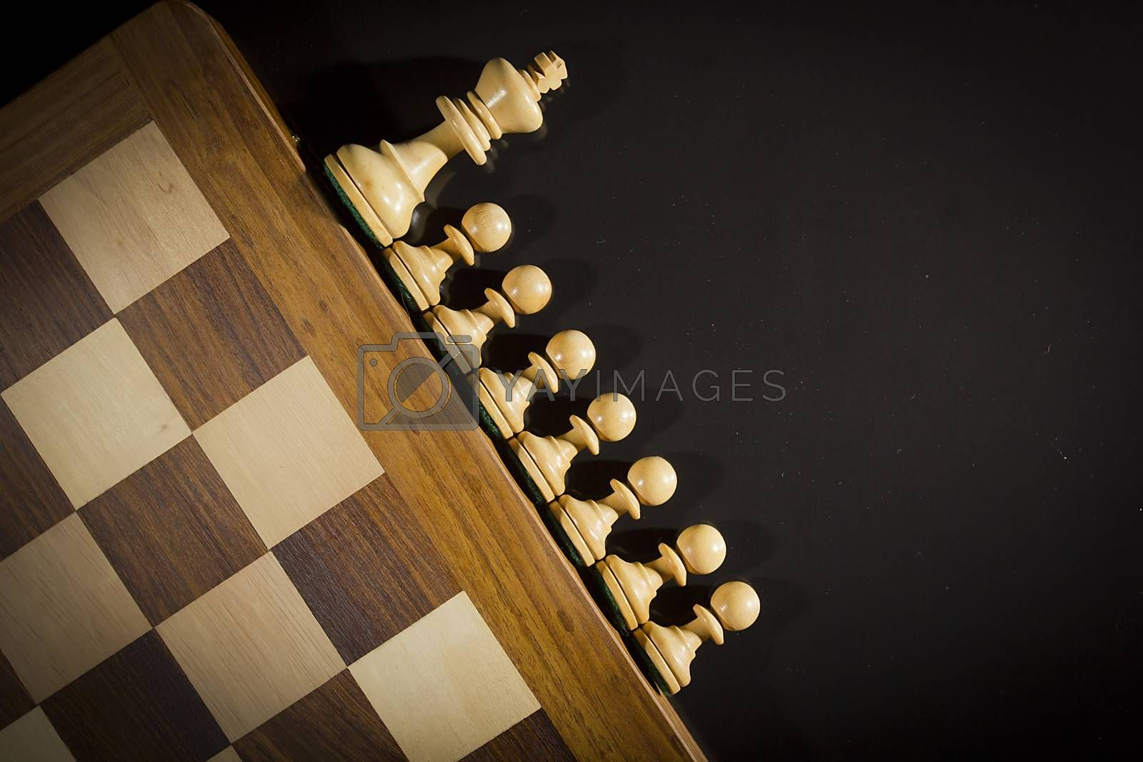 Wooden chess pieces and chess board on black background