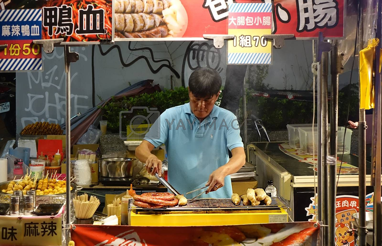 KAOHSIUNG, TAIWAN -- MARCH 2, 2018: An outdoor vendor at a night market grills fresh pork sausages.