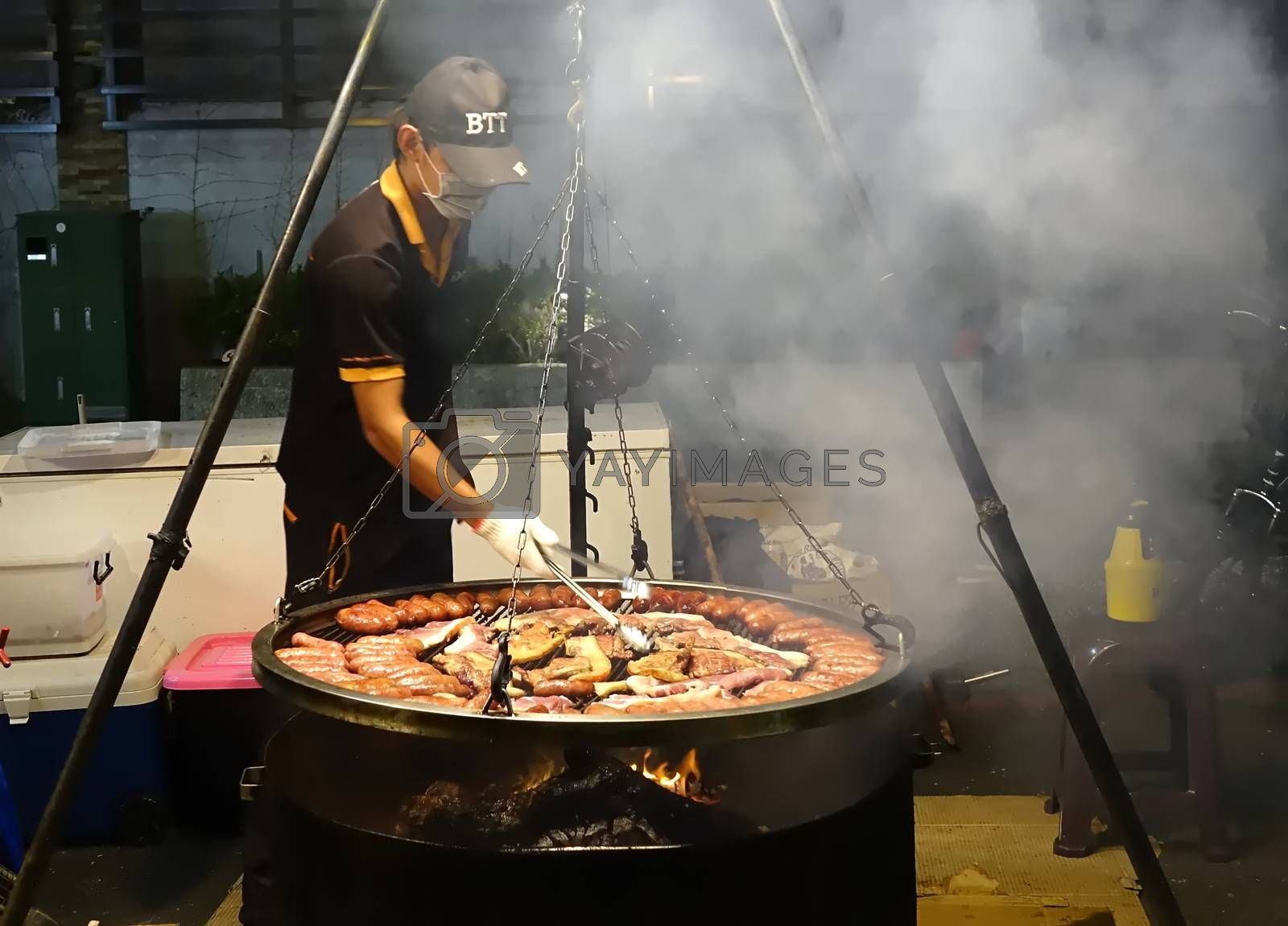 KAOHSIUNG, TAIWAN -- MARCH 2, 2018: An outdoor vendor at a night market grills fresh pork sausages and meat.