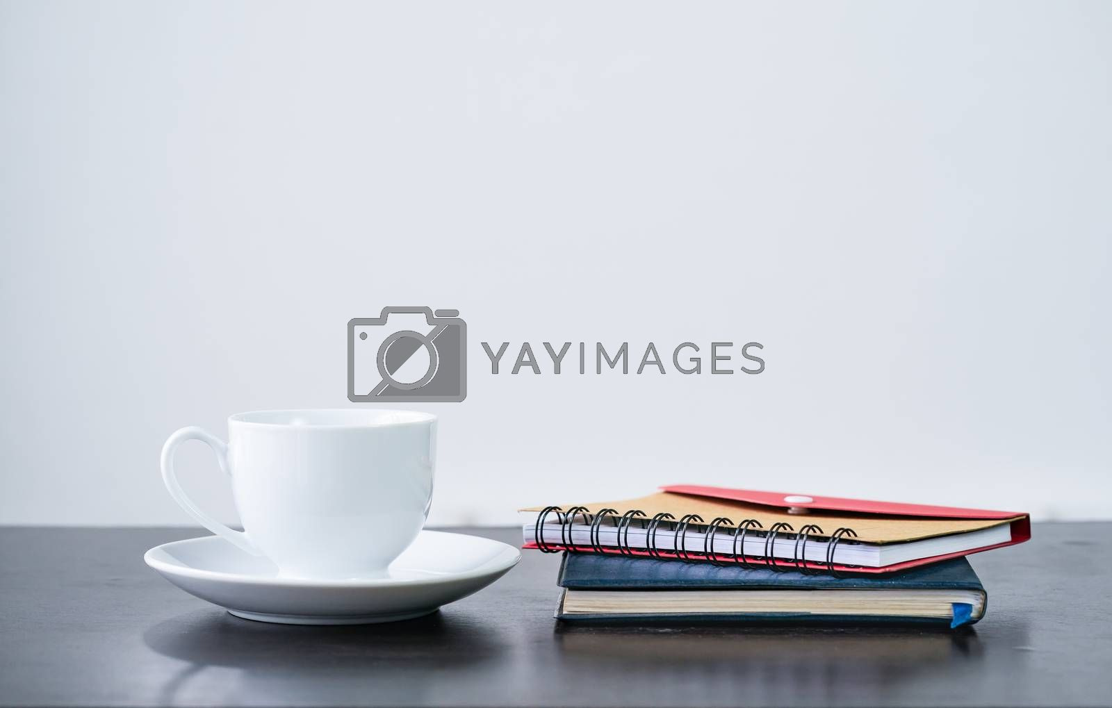 Close up Coffee cup and notebook on  wooden desk