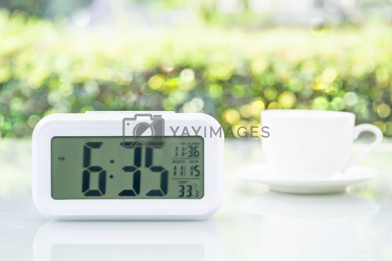 Close up Digital clock on table at office with coffee cup