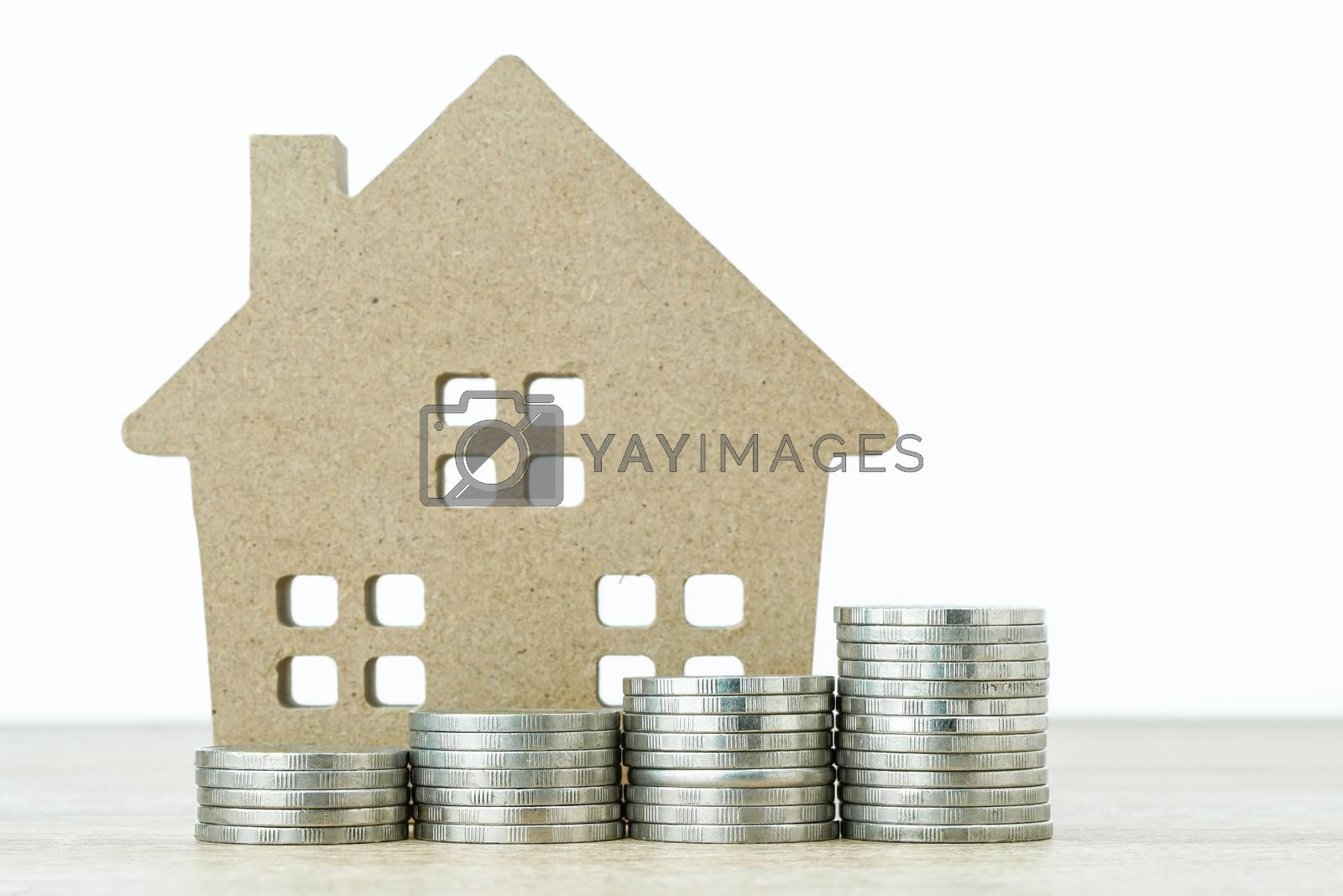House model and stack of coins on table for finance and banking concept
