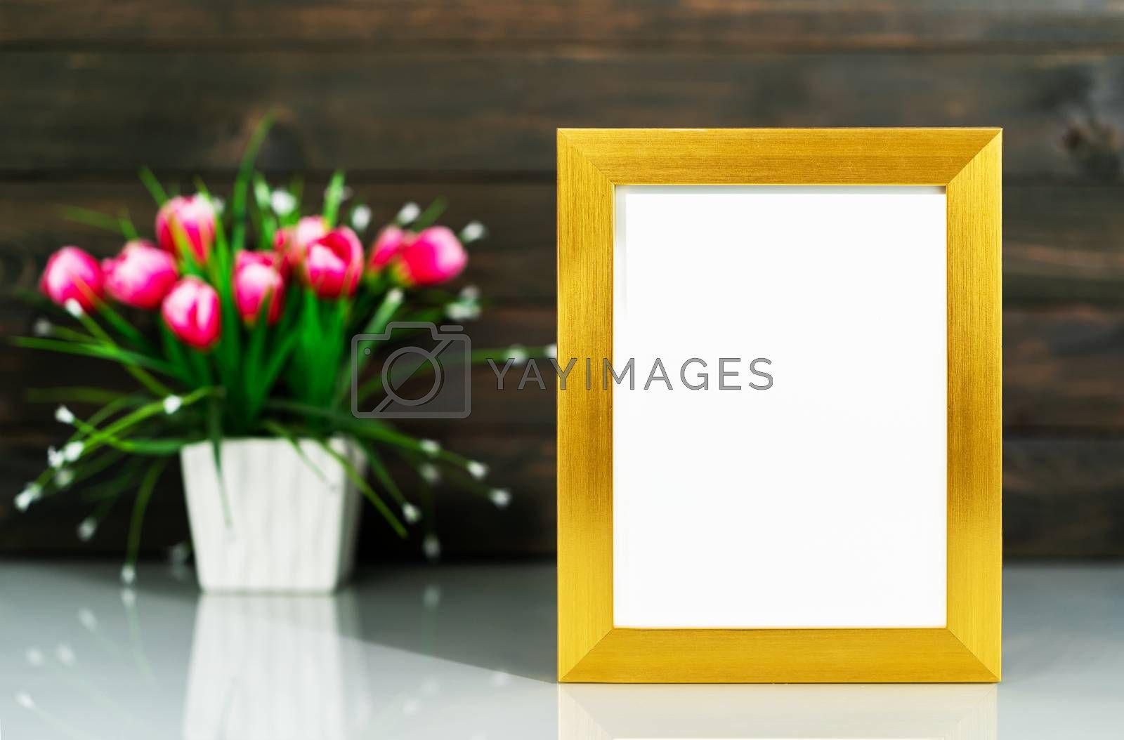 Picture mock up with golden frame and Artificial flower vase bouquet over table with wood wall background