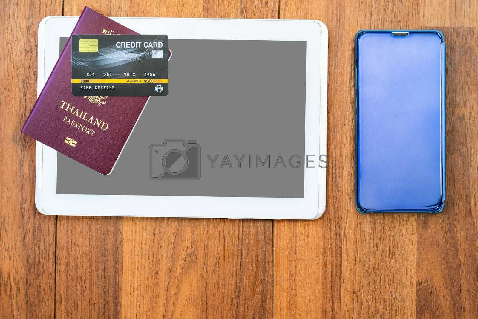 Top view Passport with credit card and smartphone and  digital tablet mock up on brown wooden desk background, Preparation for Traveling concept