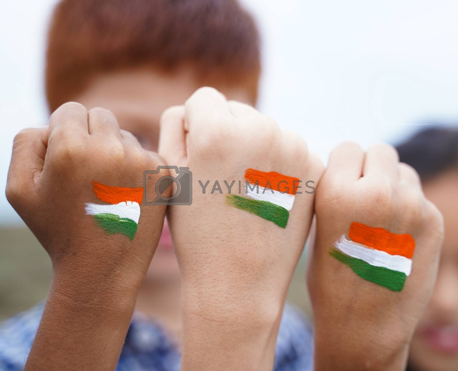 Kids fist hands painted with Indian falg during independence day or republic day celebration - concept showing of solidarity, raised fist of a protesters or patriotism.