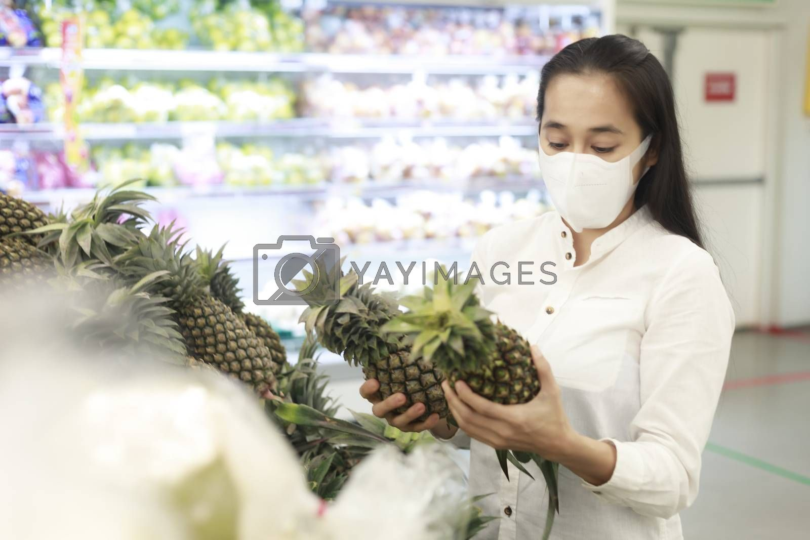 Asian woman long hair wearing protective face mask  in supermarket department store. Female, looking grocery to buy  some fruit. New normal after covid-19. Family concept. Soft focus photo.