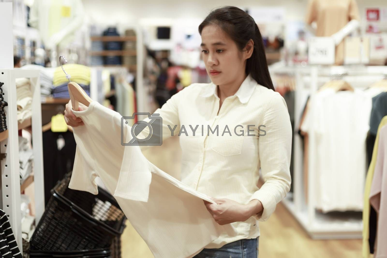 Women looking clothes in shopping mall. Asian women smileing happy to choice and tried clothes in shop. Femile holding  clothes for tried. soft focus photo select clothes