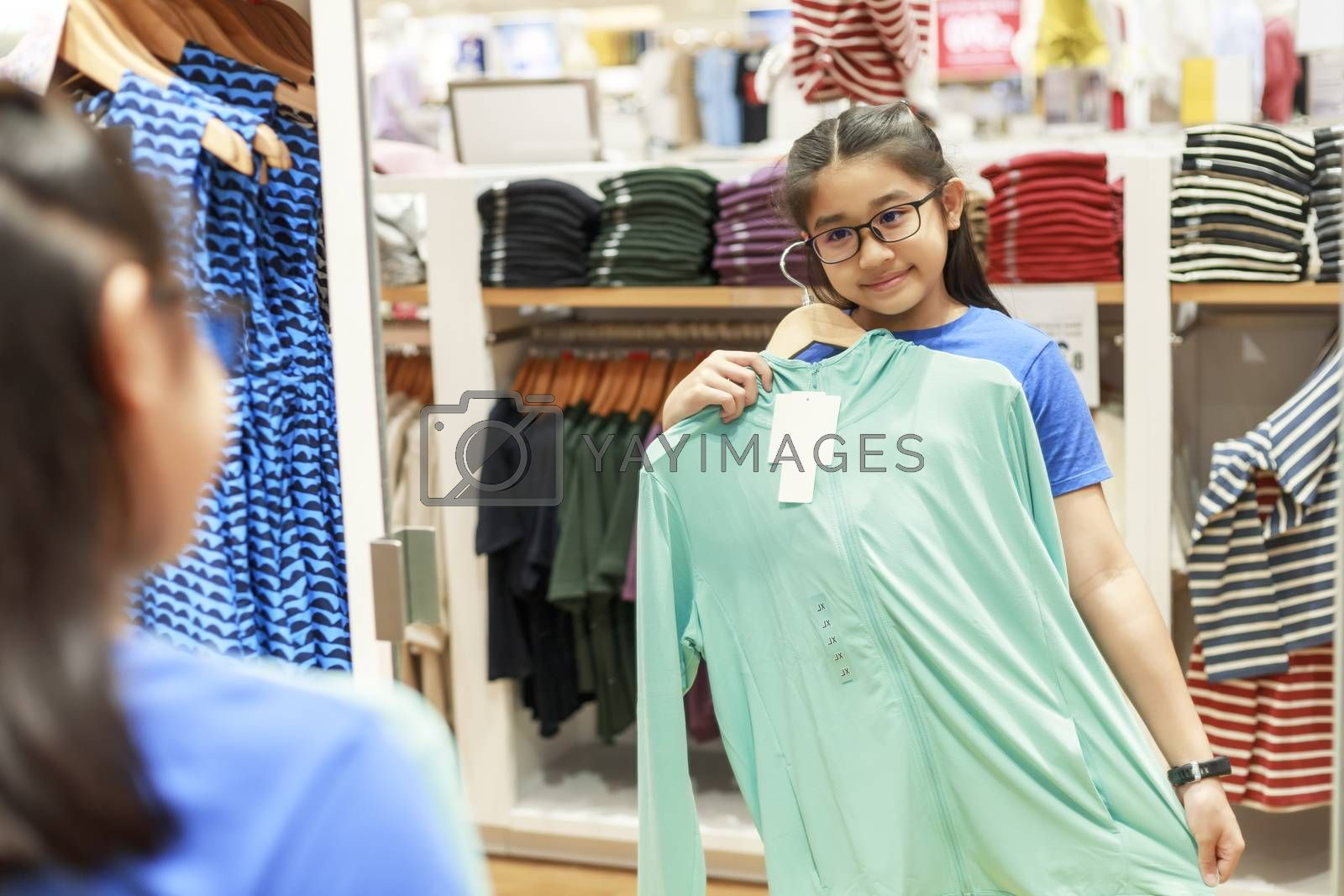 Little girl tried clothes in front of mirror in shopping mall. Asian girl smileing happy to choice and tried clothes in front of mirror in shop with copy space banner. Girl holding  clothes for tried.