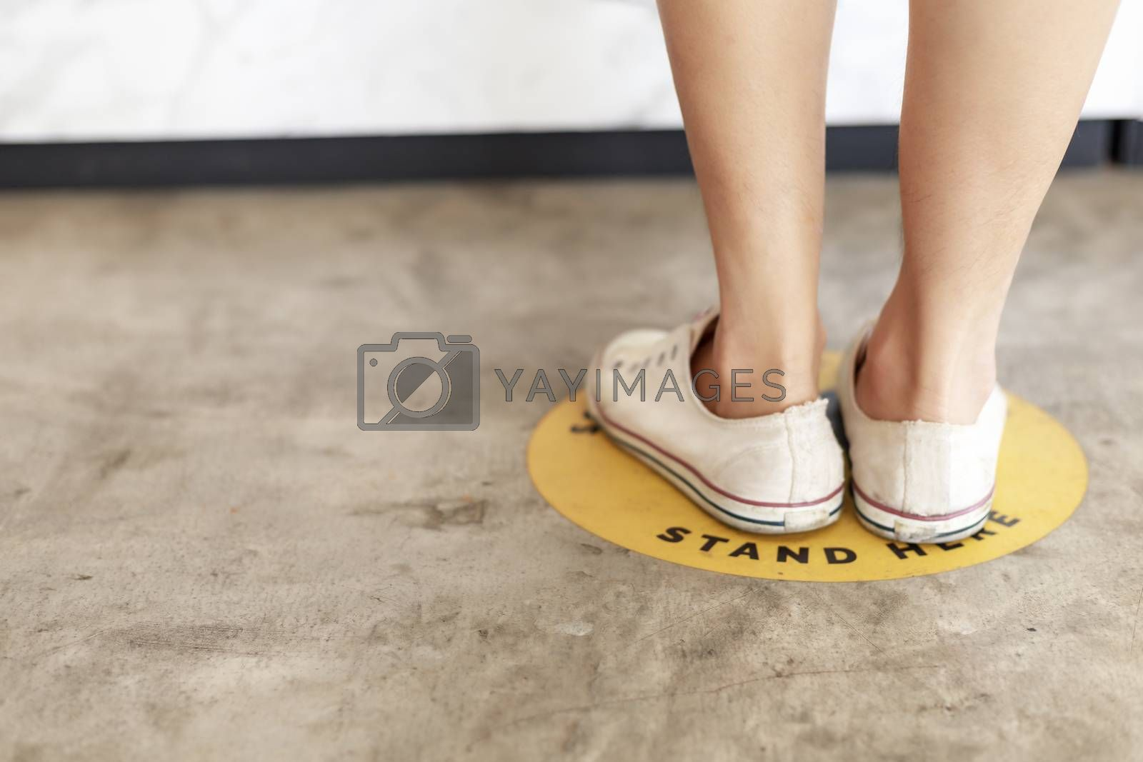 Women leg wear sneaker stand on footprint sign for stand in shopping mall, supermarket. Social distancing , COVID-19 comcept. Ccoronavirus crisis. yellow footprint sign with text caution social distance.