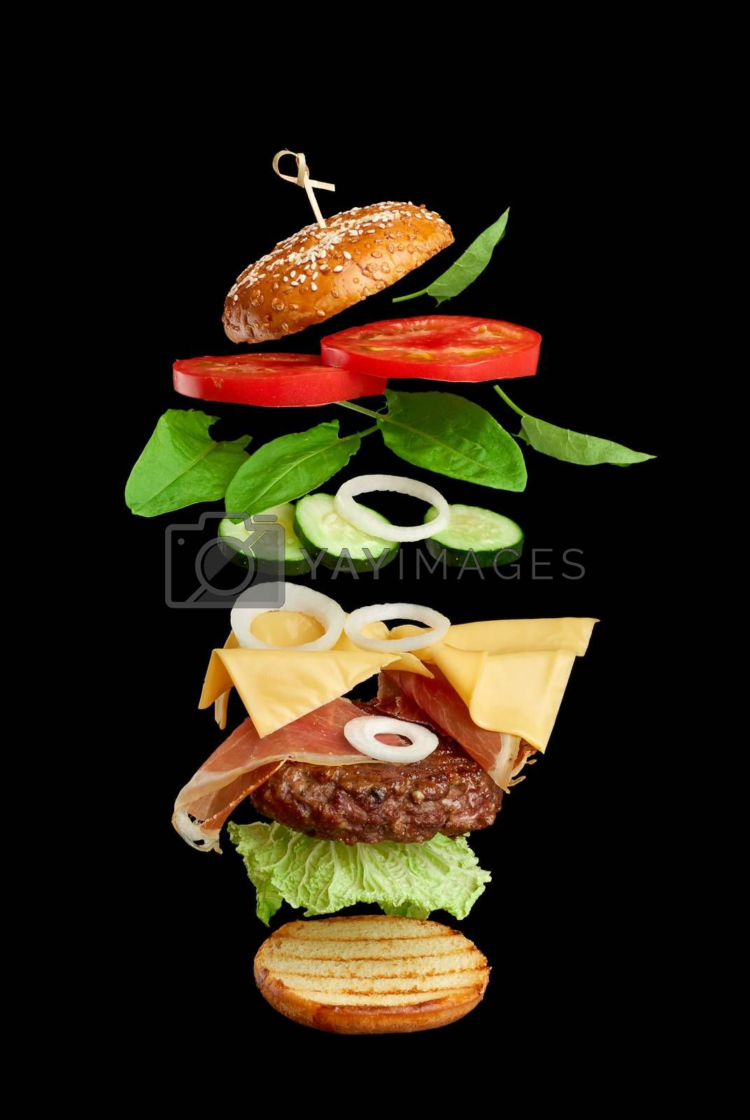 flying burger ingredients: cutlet, sesame seed bun, tomato, onion, green lettuce, cheese on black background, delicious cheeseburger, sandwich layers