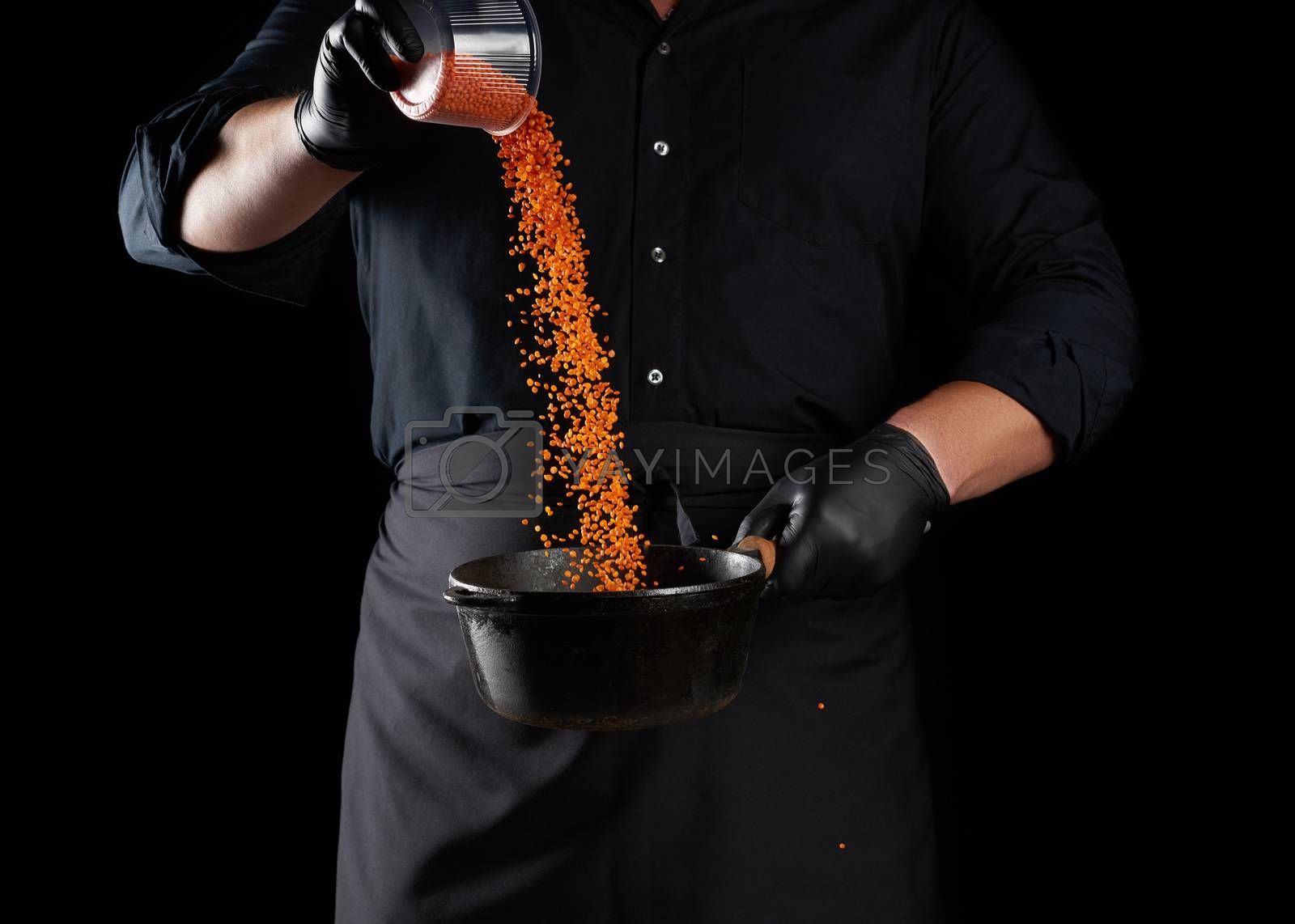 chef in black clothes and latex gloves pours raw lentils into a round cast iron pan with a handle, black background