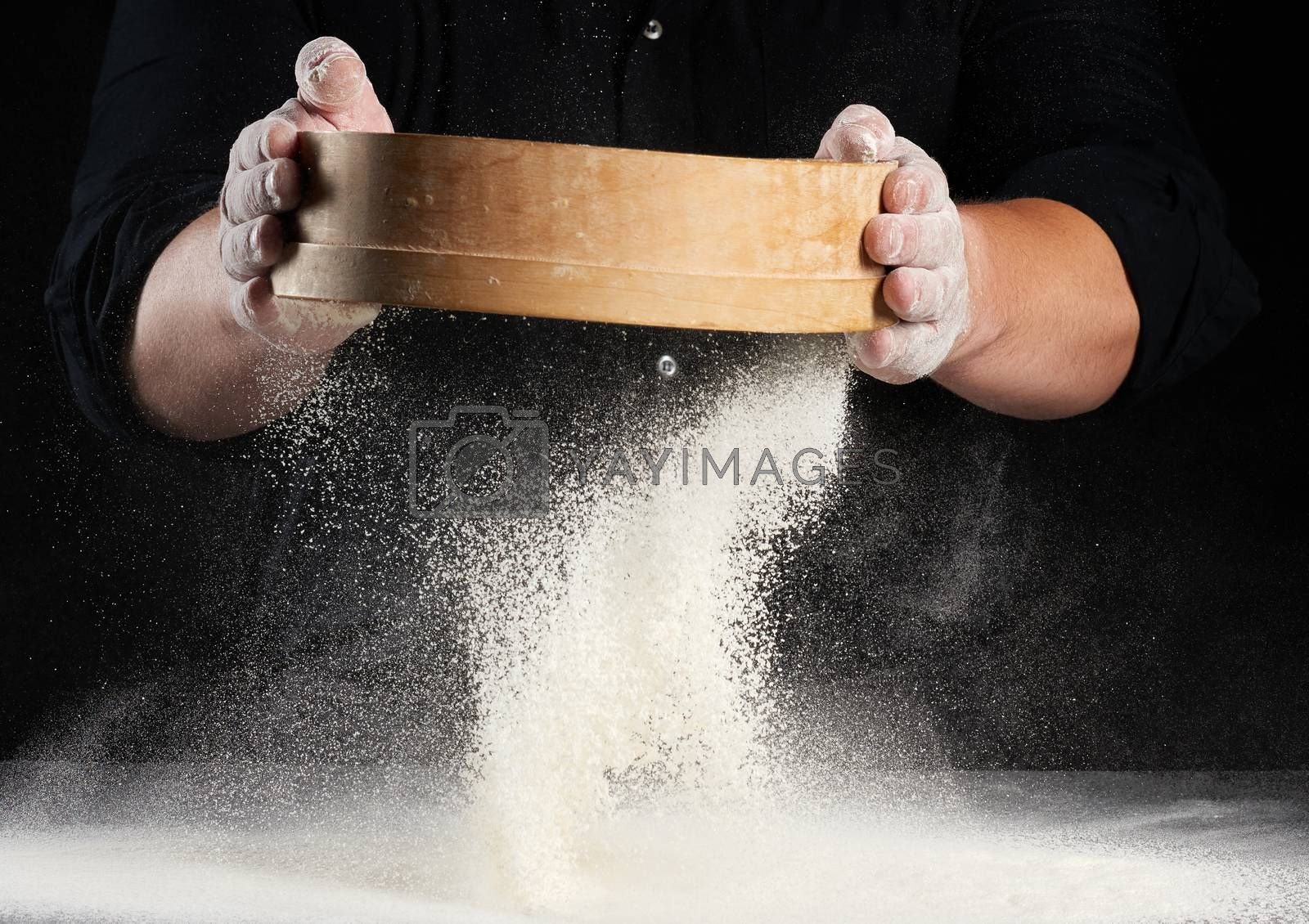 chef a man in a black uniform holds a round wooden sieve in his hands and sifts white wheat flour on a black background, particles fly in different directions