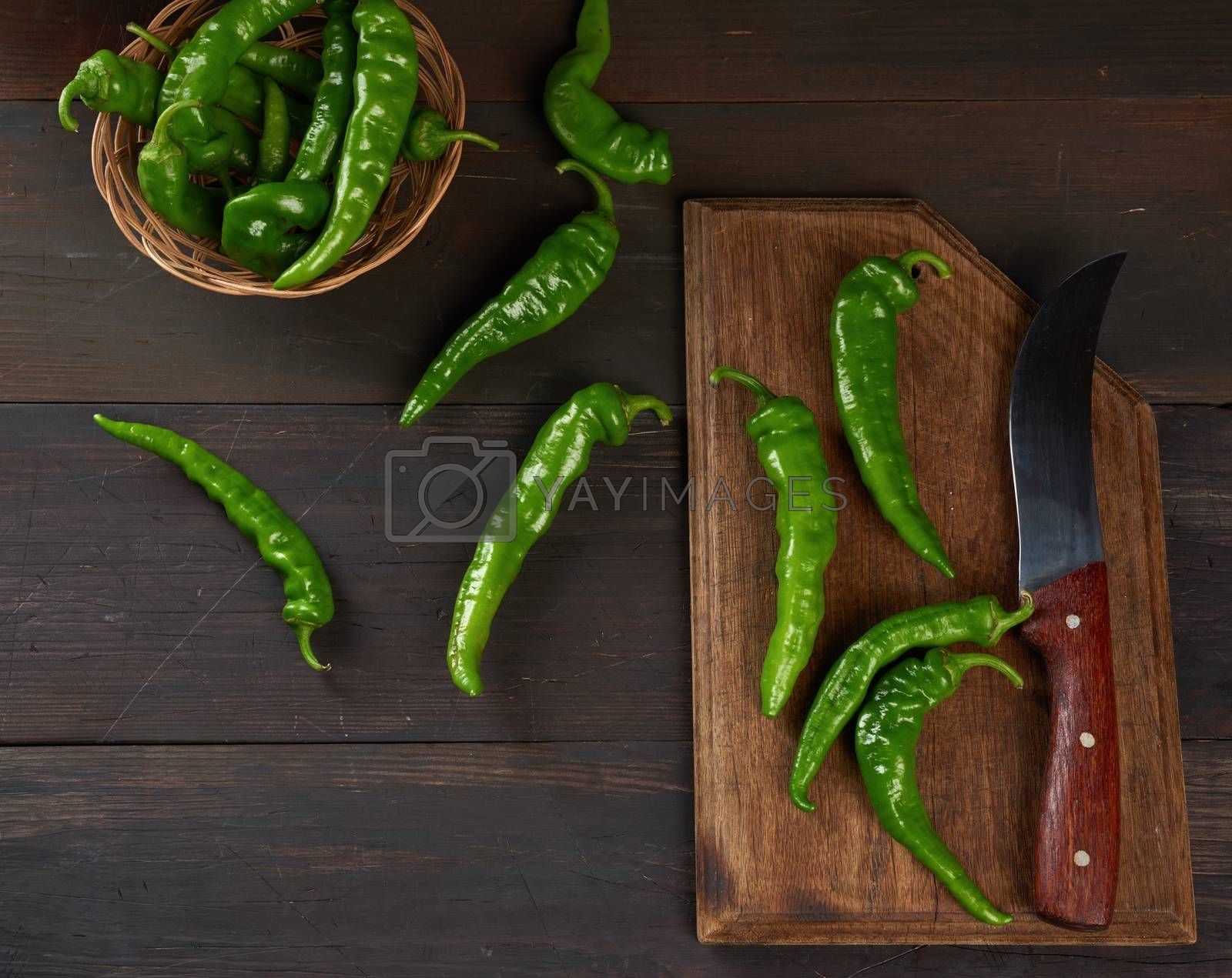 green hot pepper pods on a brown wooden table, top view