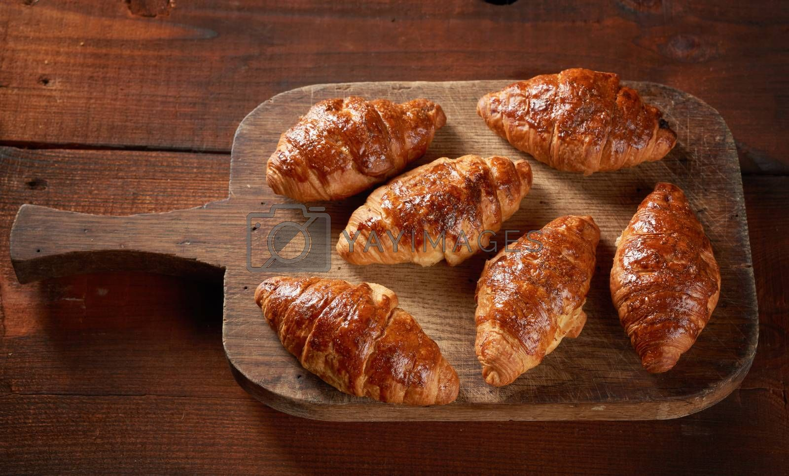 baked croissants on a wooden brown board, delicious and appetizing pastries, top view