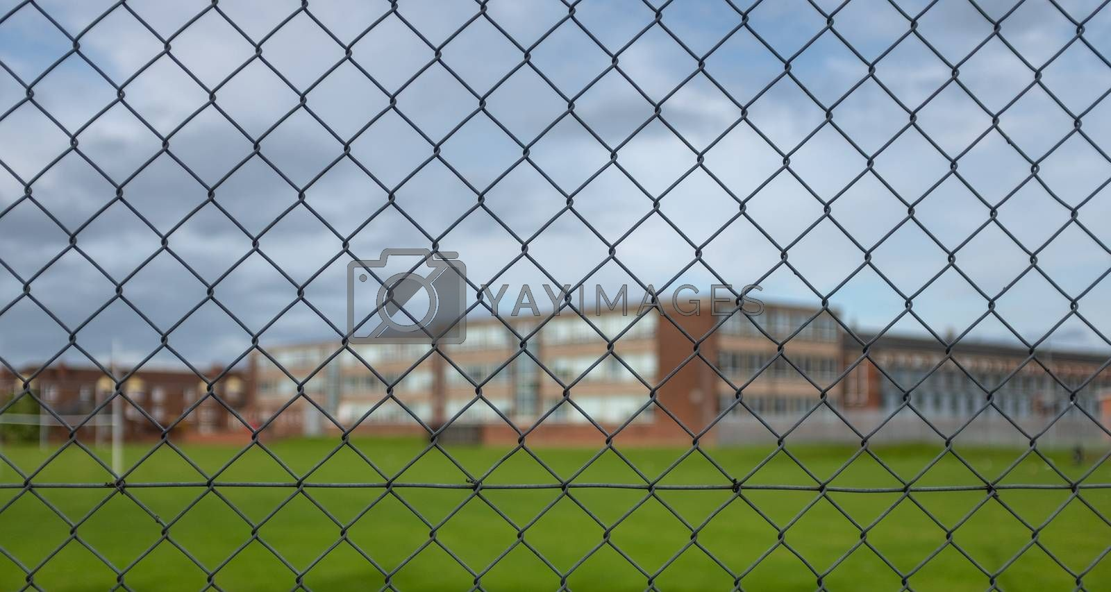 A Typical High School Building And Sports Field Under A Cloudy Sky With Focus On The Security Fence In The Foreground