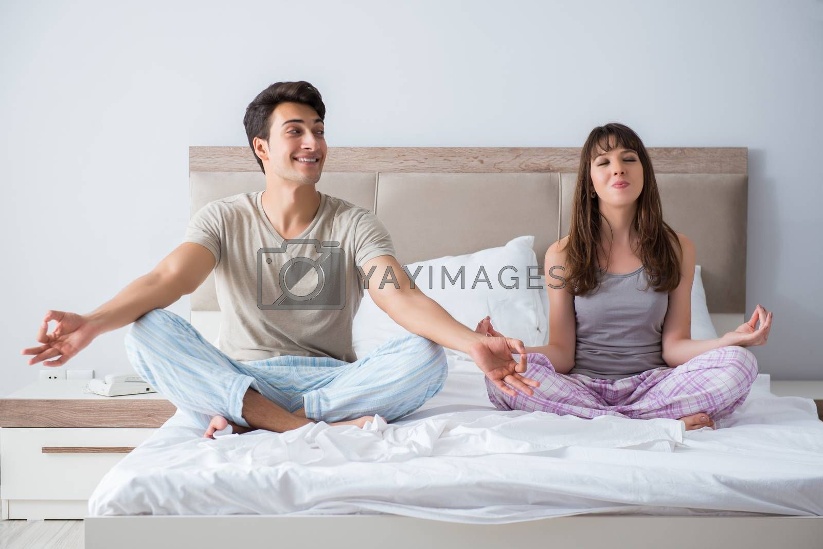 Young family meditating in the bed bedroom